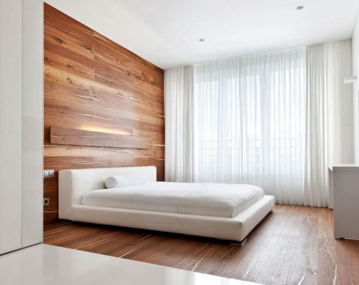 chambre adulte aménagée de style minimaliste aux murs blancs avec revêtement plancher et mur en lambris mural marron