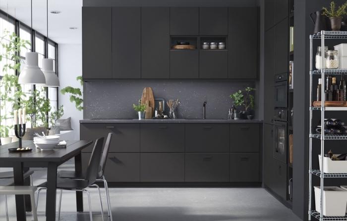 modèle de cuisine noir mat au carrelage sol gris clair et crédence gris foncé, décoration cuisine en l avec table à manger
