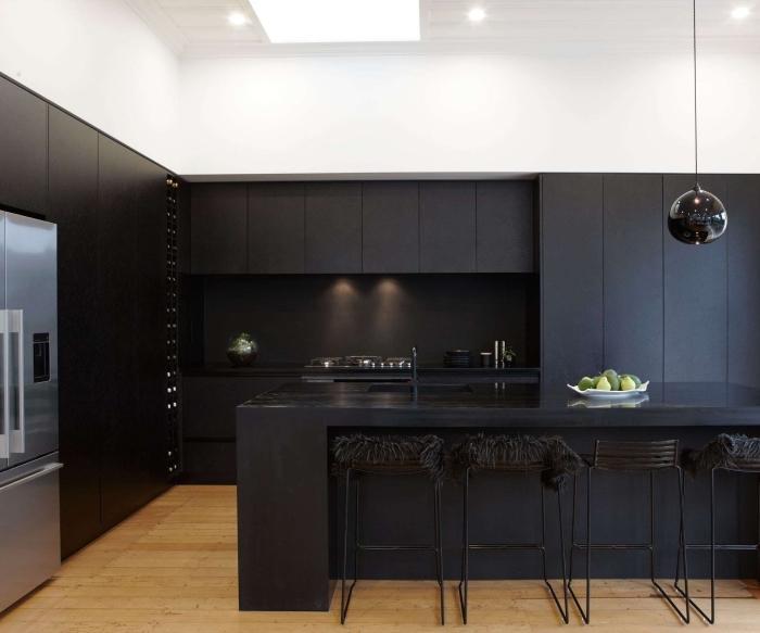 idée cuisine noir mat et bois aux murs blancs, agencement cuisine en l avec îlot central et chaises en noir mat