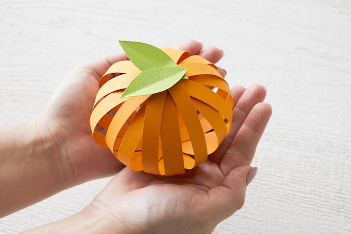 bricolage d automne, citrouille d automne en papier, bandes de papier orange avec des feuilles vertes découpées dans papier