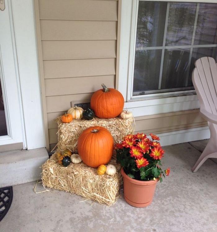 deco entree maison pour l automne avec des bottes de foin, potirons et citrouilles de tailles et couelurs variées, fleurs d automne