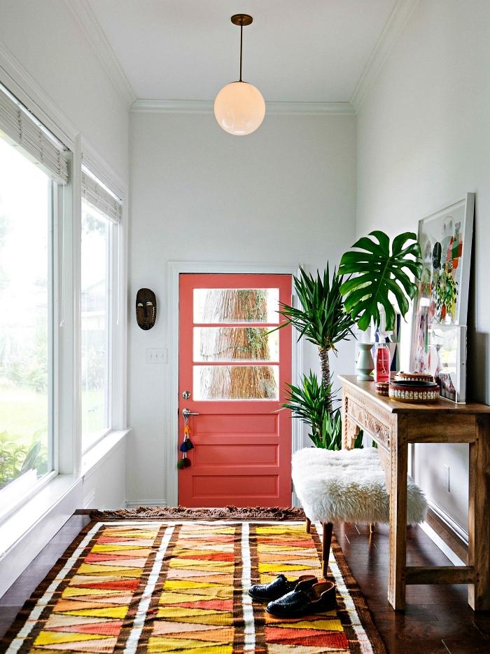 idee deco entree bohème chic avec tapis graphique multicolore, une porte d'entrée couleur corail et une console bois vintage