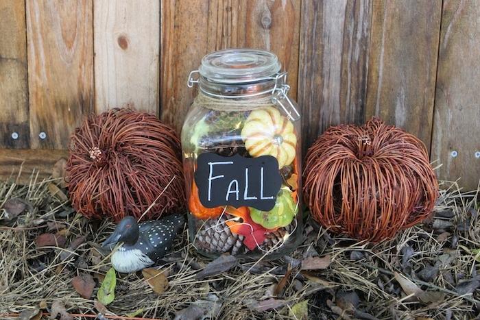 deco jardin a faire soi meme theme automne, citrouilles artificielles en branches d arbre et bocal rempli de citrouilles, pommes de pin et autres decorations