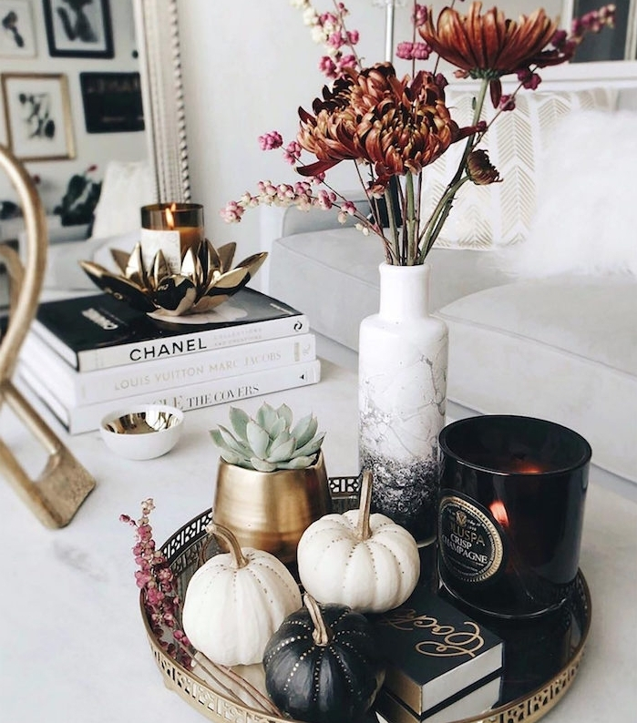 idee deco table basse avec des potirons décorés, deco citrouille dans un plateau avec bougie et bouquet de fleurs d automne dans vase effet marbre