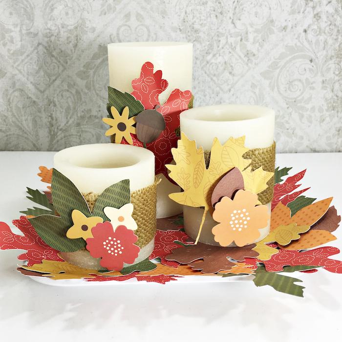 bougies customisées de bande de jute couleur or, fleurs et feuilles de papier sur un tapis de feuilles mortes de papier