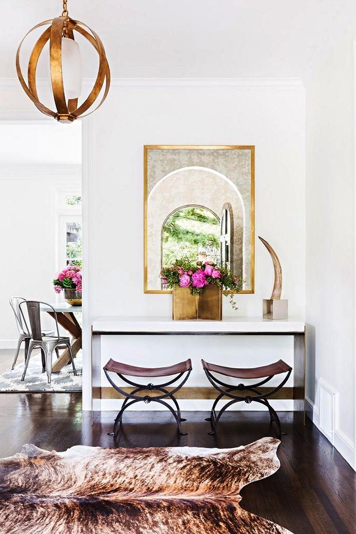 decoration maison moderne avec meuble d'entrée au design épuré, un tapis peau de bête et un poster mural abstrait