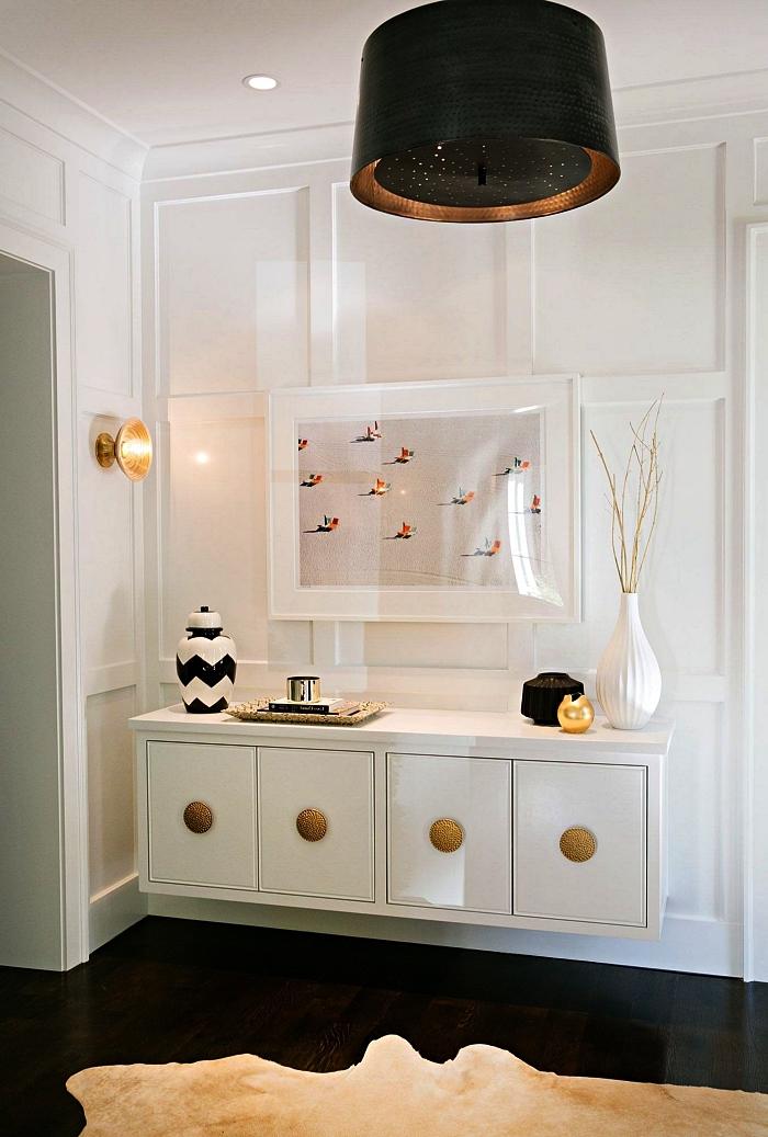 hall d'entrée au sol noir avec meuble flottant blanc aux accents dorés fixé au mur en panneau bois blanc