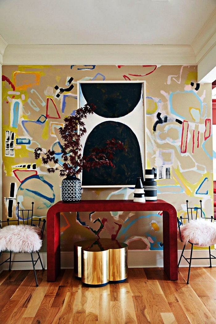 decoration maison moderne, entrée chic avec console design rouge, tabouret en laiton et un mur au papier peint graphique et coloré