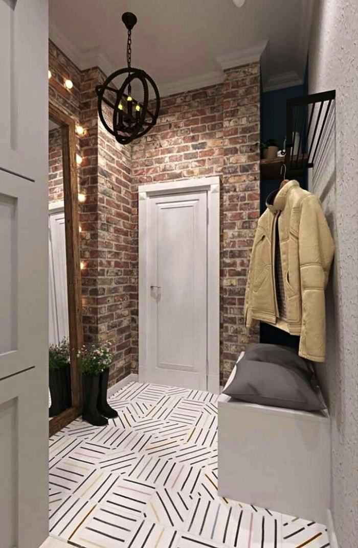 petit hall d'entrée au sol graphique et aux murs imitation briques équipé d'une banquette et d'une niche murale avec étagères