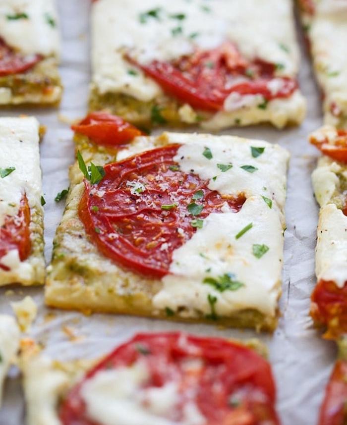 apero dinatoire idee facile, carrés de feuilleté avec tranches de tomate, fromage et persil haché en top