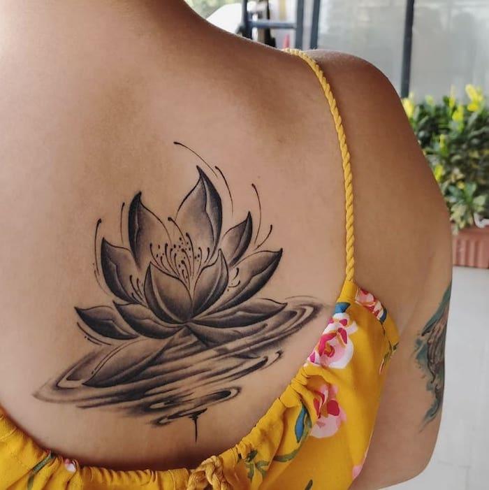Dos femme tatouage lotus dans l'eau, zen tatou à grande signification fleur de lotus, symbole tatouage fleur de lotus
