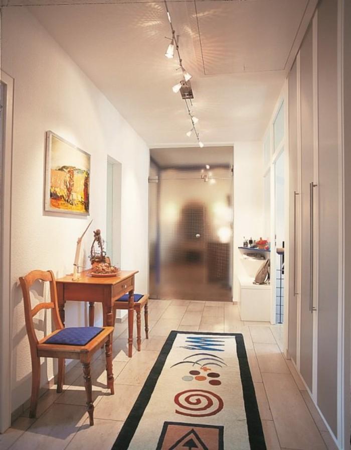 Tapis long coloré à motif géométrique, table et deux chaises, étagère couloir étroit, éclairage artificiel pour couloir
