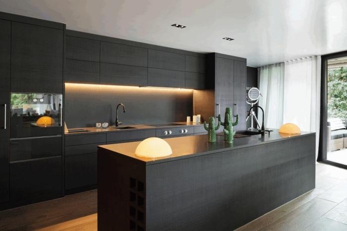 modèle de cuisine tendance couleurs foncées, design cuisine ouverte linéaire avec îlot central en noir mat et bois