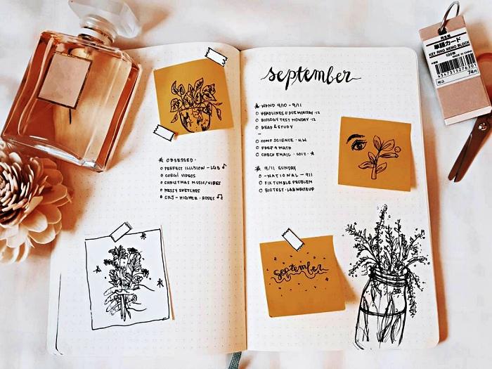 système d'organisation avec bullet journal idées de mise en page d'un planning mensuel, page double d'un bullet journal décoré de post-it et de dessins naturalistes