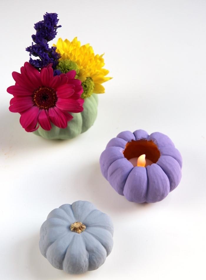 exemple de deco automne facile a faire avec des potirons décorés de peinture et vidés pour faire un photophore ou vase avec bouquet de fleurs à l intérieur