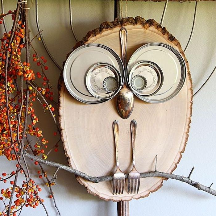 rondin de bois motif hibou figuré avec des couvercles de bocal, cuillère et fourchettes, idee deco murale a faire soi meme