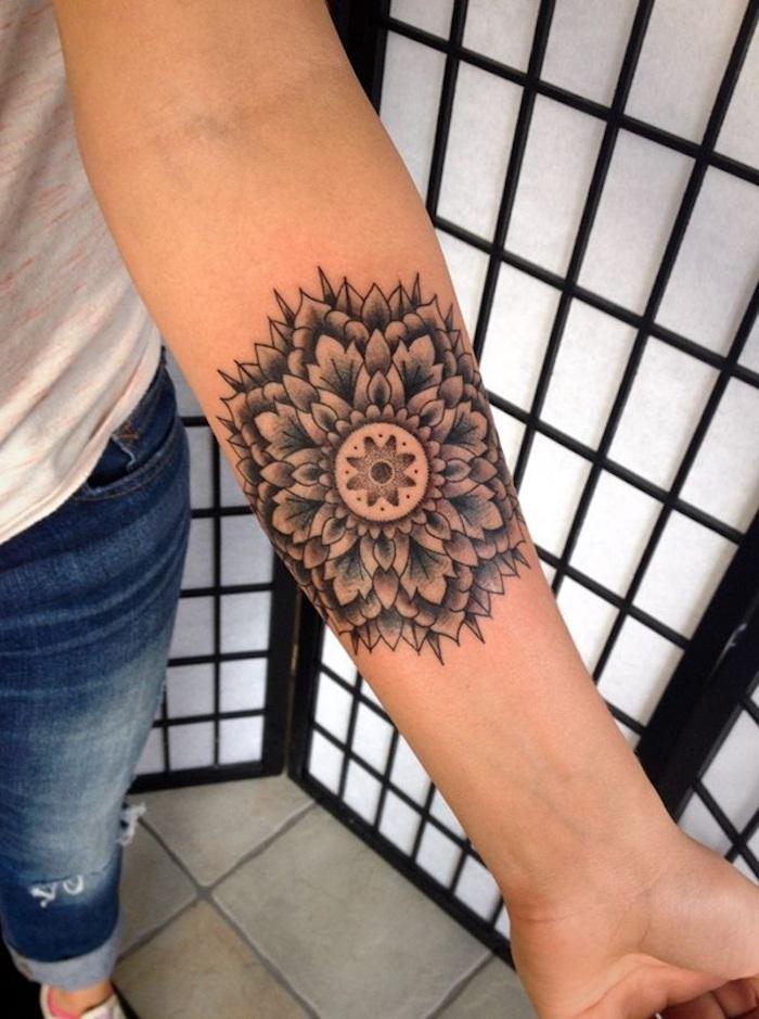 Mandala tatouage sur l'avant bras, femme jean long et t-shirt blanche, dessin de fleur lotus mandala