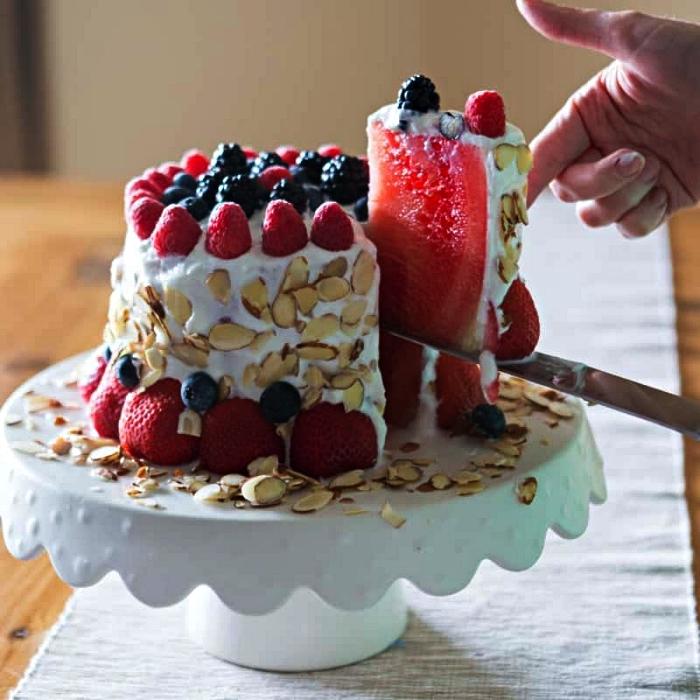 gâteau de pastèque nappé de crème au mascarpone au décor de fruits rouges et d'amandes effilées, idée de dessert facile et rapide et original