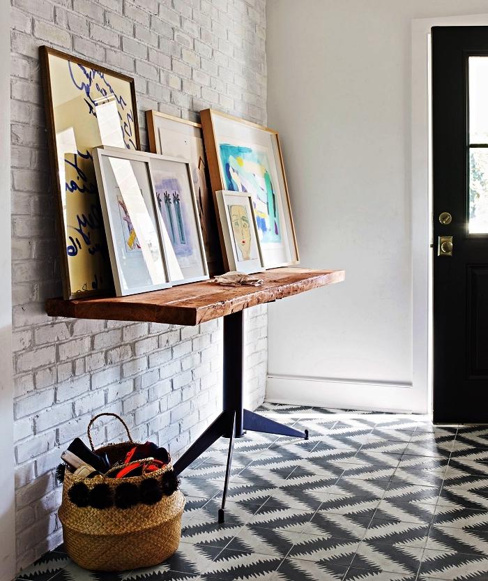 idee deco entree avec accumulation de cadres sur une table industrielle en bois rustique, une entrée au mur en briques et au sol en carreaux de ciment
