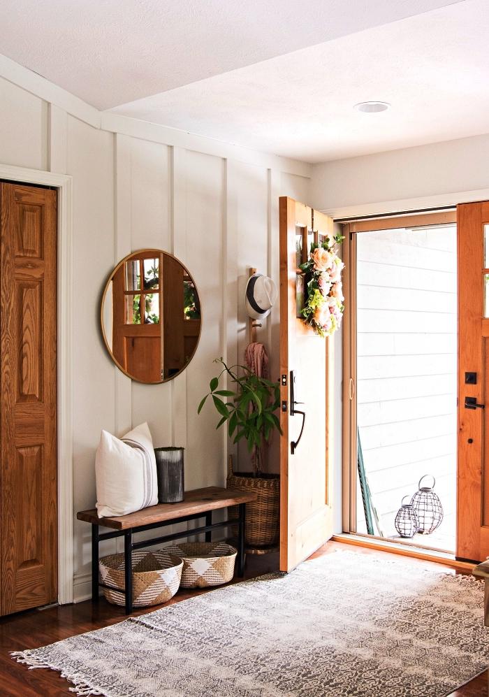 aménagement d'un hall entrée avec banquette entrée bois et métal, paniers de rangement en osier et un grand miroir rond