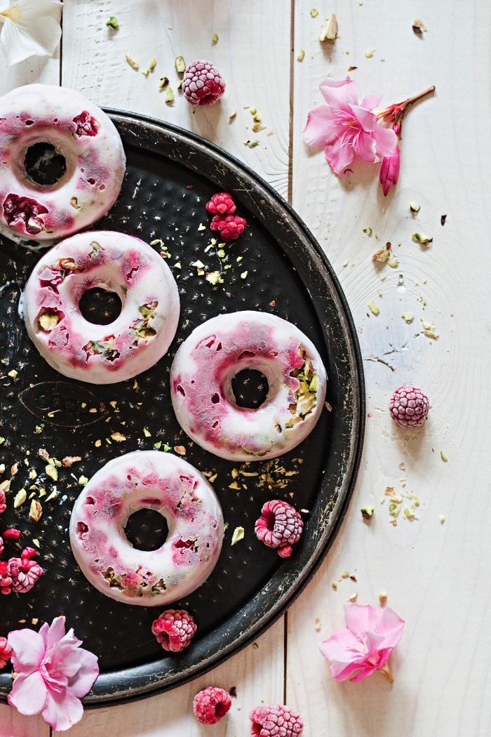 recette estivale de petit dessert frais au yaourt glacé, pistaches et framboises surgelées en forme de donuts