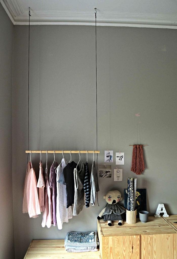 aménagement coin dressing chambre d'enfant avec penderie suspendue au mur en dessus du placard bois