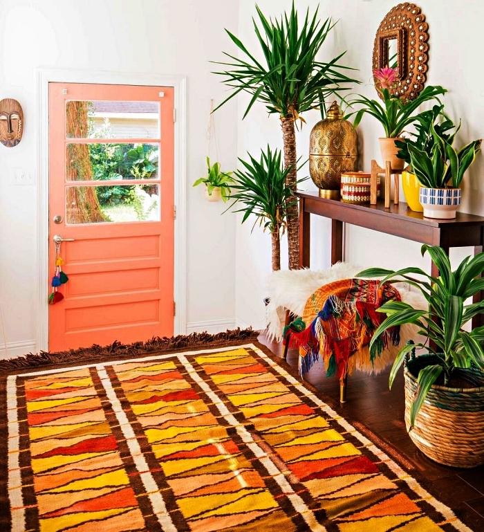 décoration d'entrée bohème chic avec des plantes vertes variées, des accessoires en bois et osier et un tapis ethnique multicolore