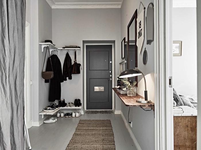 idee deco entree de style scandinave aux murs peints en gris, aménagement d'un hall d'entrée avec console murale en bois et penderie murale minimaliste