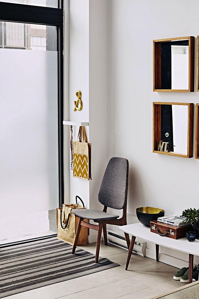 aménagement entrée minimaliste avec petite table basse scandinave en bois et blanc, une chaise vintage gris et des miroirs à cadres bois