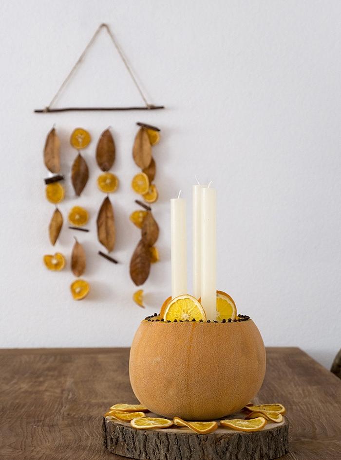 mobile deco murale bois flotté avec tranches d orange séchées et feuilles d automne, centre de table potiron avec bougies sur rondin de bois et tranches d orange