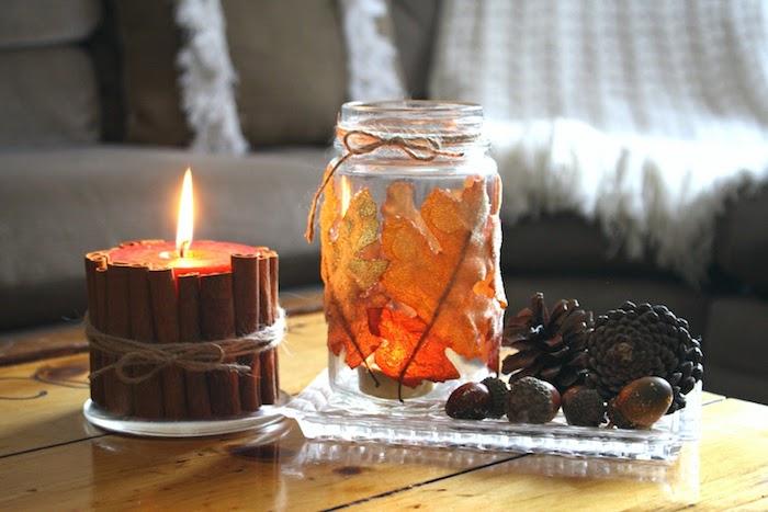 bougie entourée de batons de cannelle à coté de pot en verre customisé de feuilles mortes, pommes de pin et glands dans assiette de verre