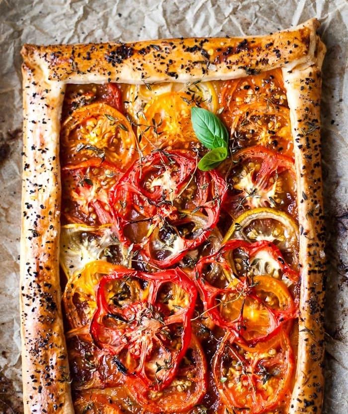 exmeple de tarte aux tomates avec des tranches de tomate de couleurs variées et herbes fraiches pour garnir