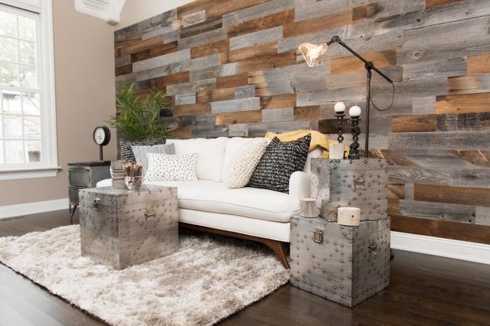 salon cozy avec plancher bois foncé couvert de tapis moelleux blanc et mur habillée en planches bois gris et marron