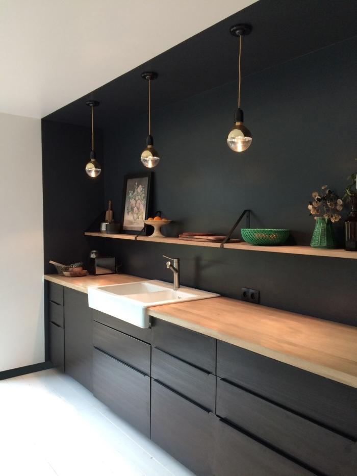 agencement cuisine linéaire en noir avec plan de travail bois, déco cuisine noire et bois avec plafond et plancher blancs