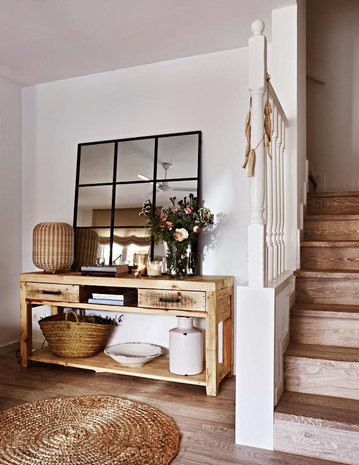 déco entrée maison de campagne avec une commode en bois massif, un grand miroir fenêtre et des accessoires en rotin