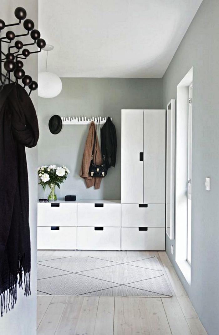 meuble d'entrée ikea avec multiples rangements combiné avec des patères en blanc et noir, entrée de style scandinave aux murs gris clair