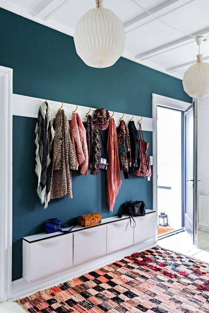 deco entree en blanc et bleu canard, entrée avec meuble à chaussures ikea, des crochets au mur et un tapis graphique multicolore