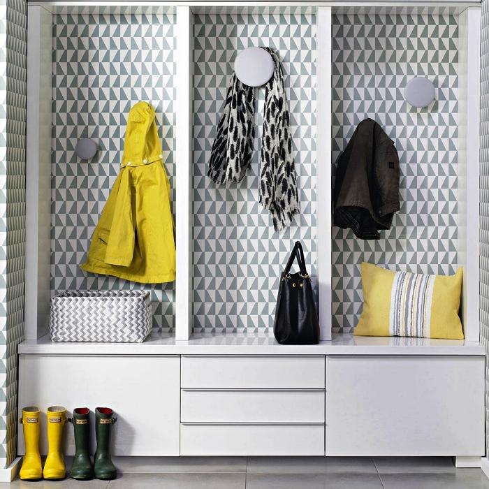 vestiaire blanc customisé avec du papier peint graphique et des patères rondes en gris, déco d'entrée moderne en gris et jaune