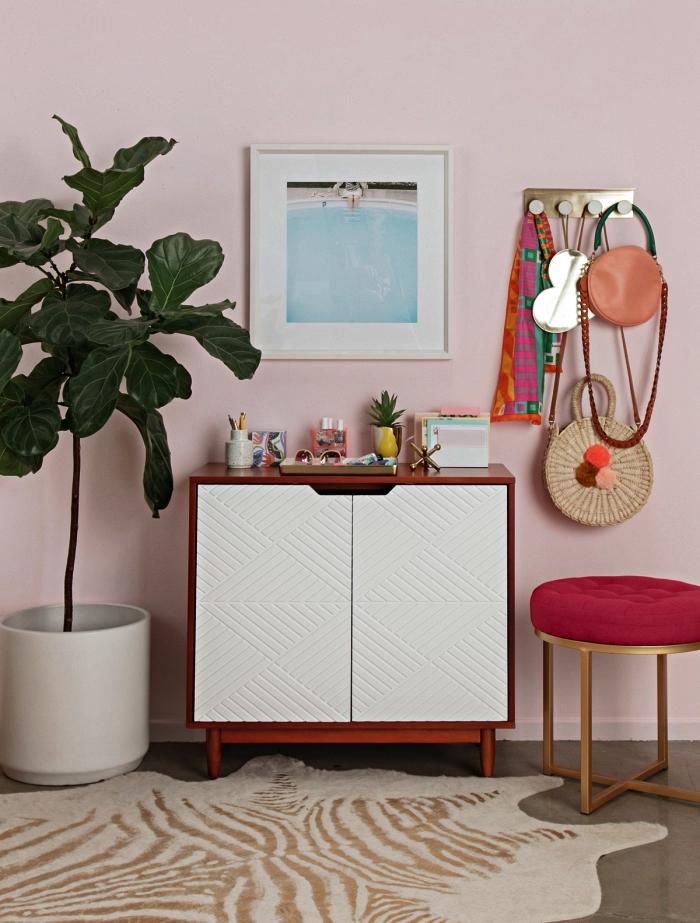 deco entrée rose avec petit meuble vintage en bois et blanc, une patère laiton et un tabouret design en velours et laiton