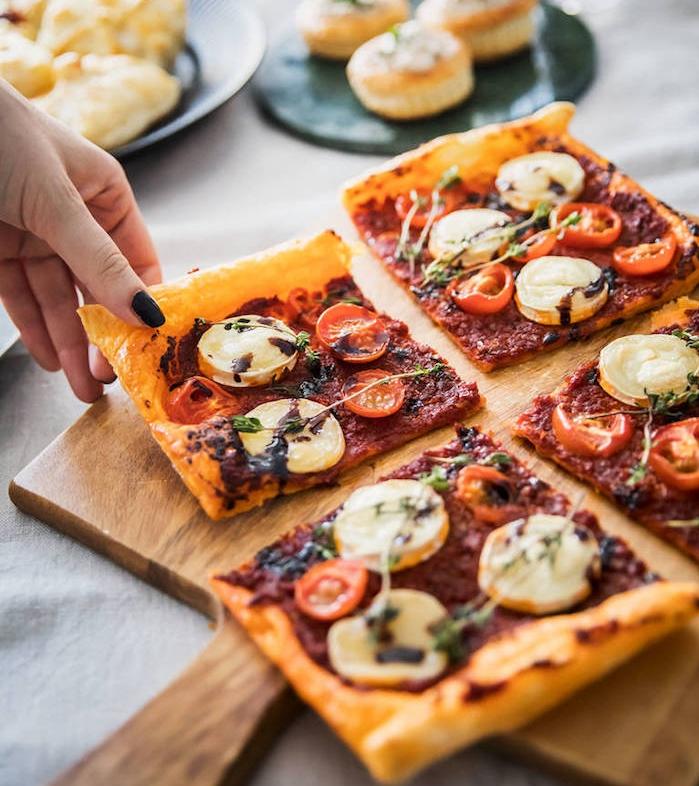 mini pizza feuilletée dans pate avec purée tomates, rondelles de fromage chevre, tomates cerise et du thym frais