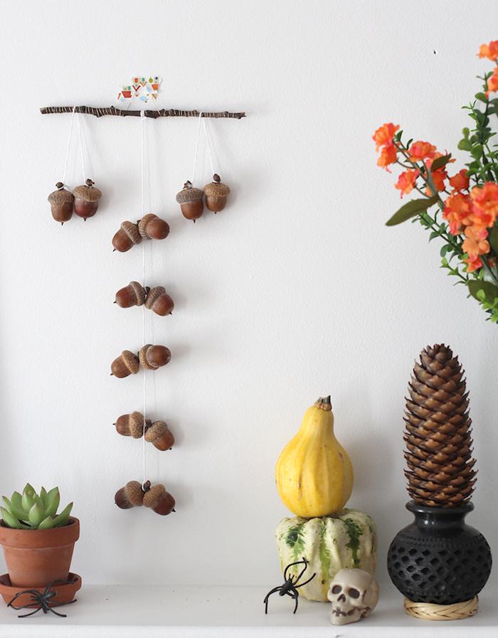brindille bois flotté avec des glands suspendus sur des fils pour decorer un mur blanc, petits potirons, deco halloween