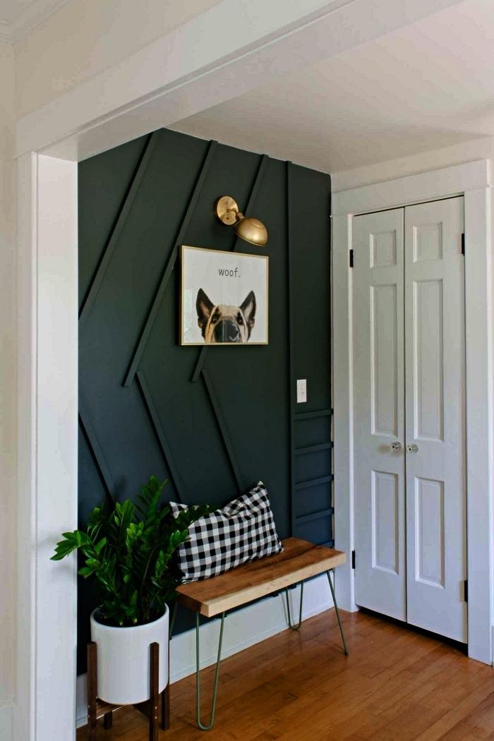 un pan de mur peint en en vert foncé pour délimiter un coin de l'entrée avec banc décoratif à pieds épingles