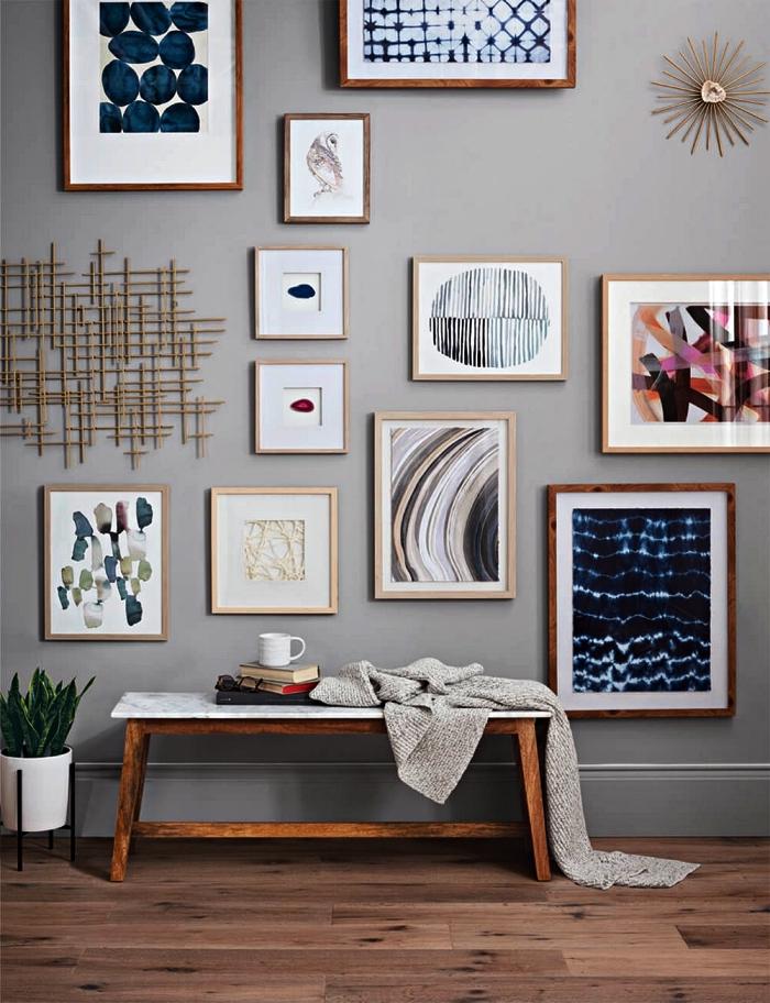 idee deco entree avec un mur de cadres sur fond gris et un banc d'entrée décoratif en bois et marbre