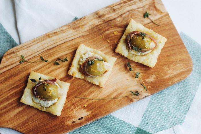 carré de feuilleté avec fromage aux herbes fraiches, prosciutti et olives, amuse bouche pate feuilletée
