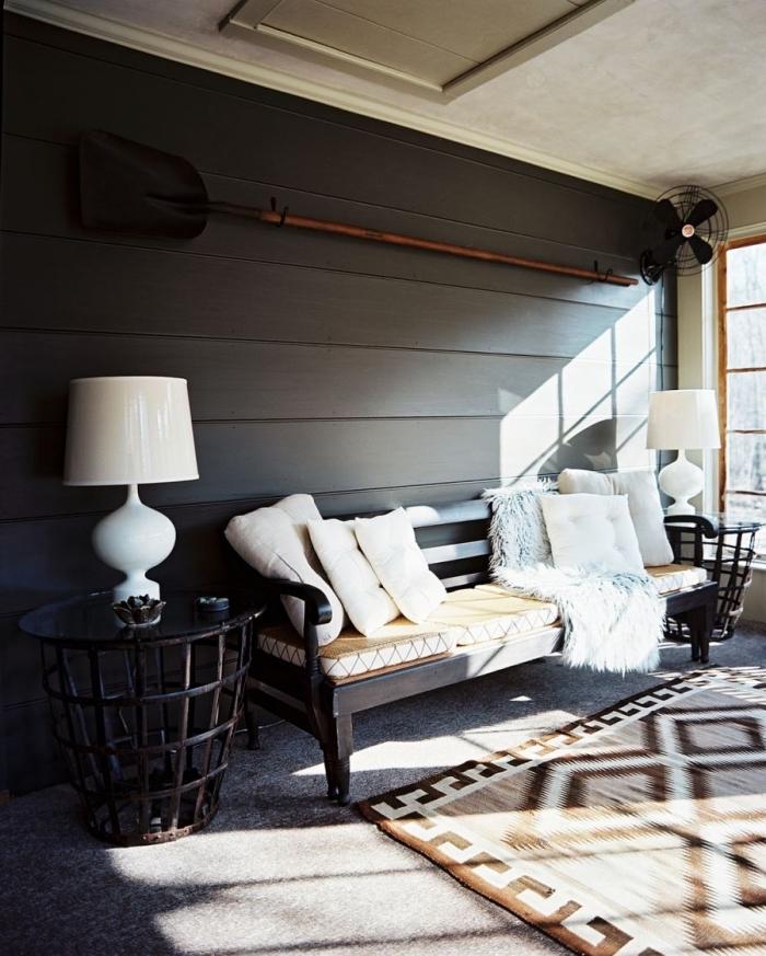 exemple lambris bois large foncé, déco de salon cozy avec murs foncés et meubles en bois, accessoire déco plaid en faux fur