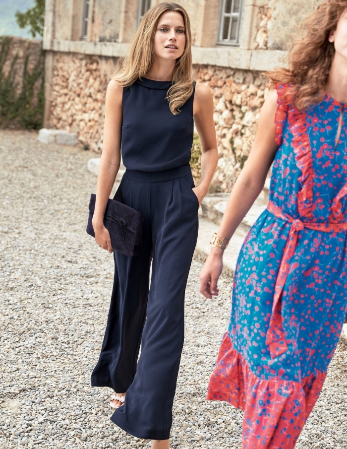 comment bien s'habiller pour une soirée, modèle tailleur femme chic de couleur bleu foncé avec pochette noire
