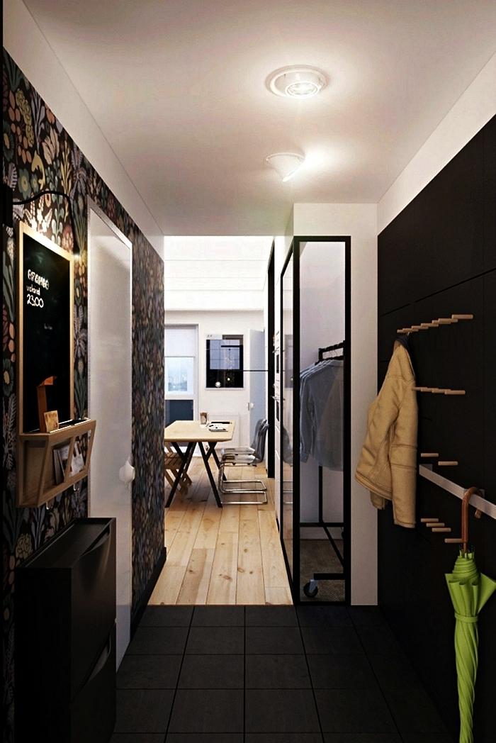 entrée en noir et blanc au mur d'accent en papier peint imprimé tropical aménagée avec meuble à chaussures ikea et des patères en bois