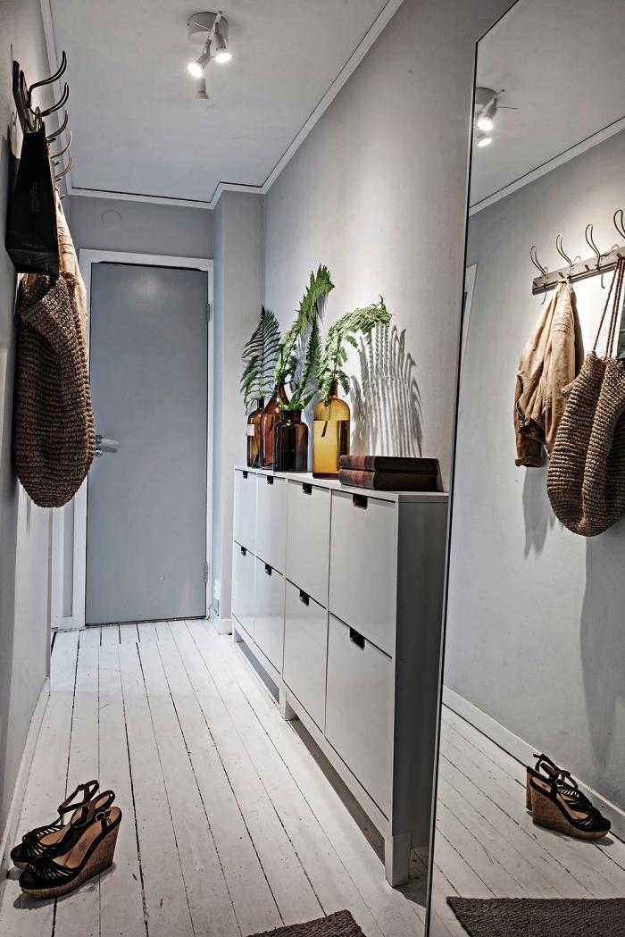 aménagement entrée étroite en gris et blanc avec meuble à chaussures ikea et un grand miroir posé contre le mur