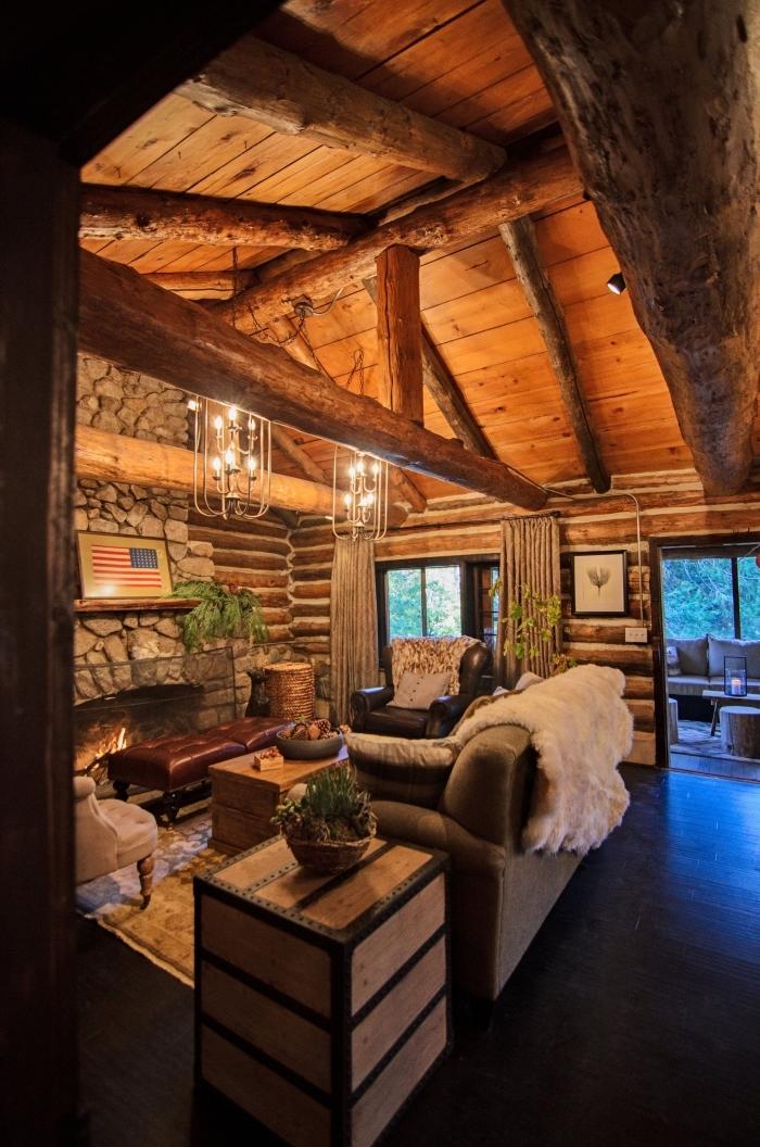 aménagement salon rustique avec murs en pierre et planche de bois brut, décoration poutres apparentes salon