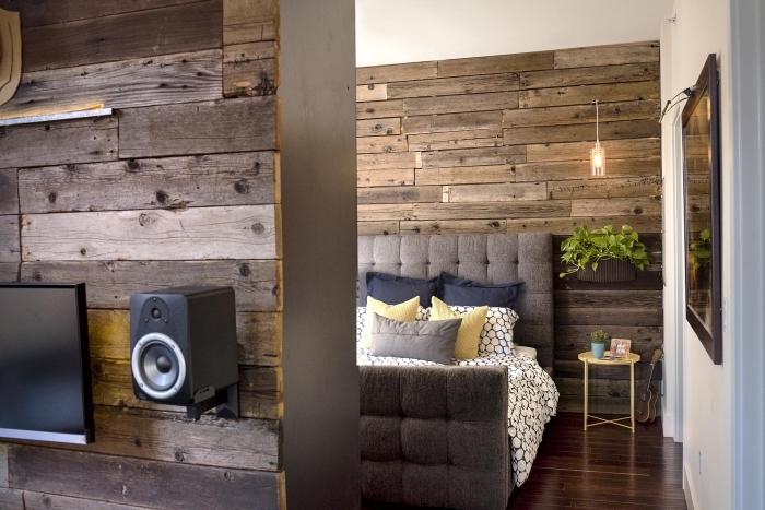 décoration chambre de style rustique avec murs en planche de bois brut, modèle tête de lit boutonnée en gris